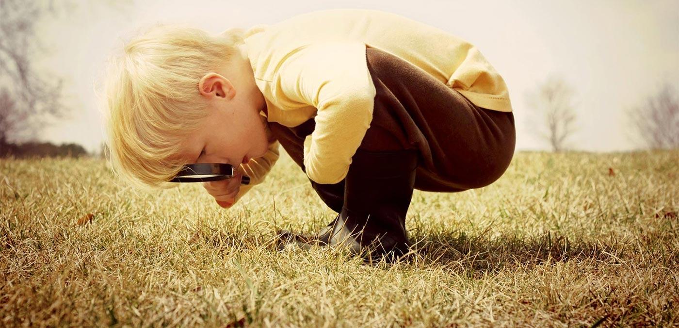 boy exploring child grass carousel