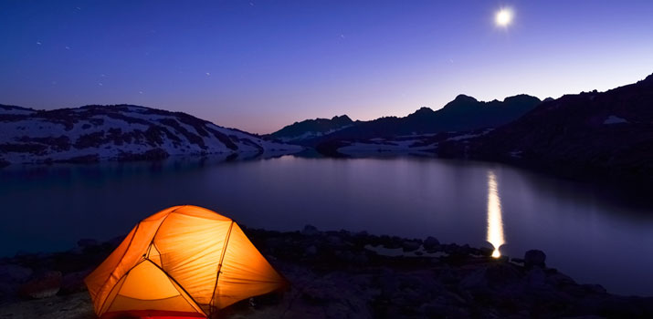 Tent lit up at night with a full moon beside a lake