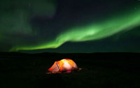 Lit up tent in darkness except for northern lights