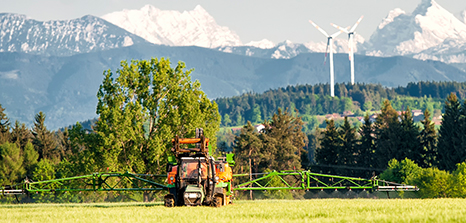 Farm spraying their crops with wind turbines in the background