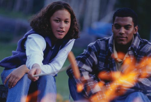 Man and woman roasting marshmallows on a campfire