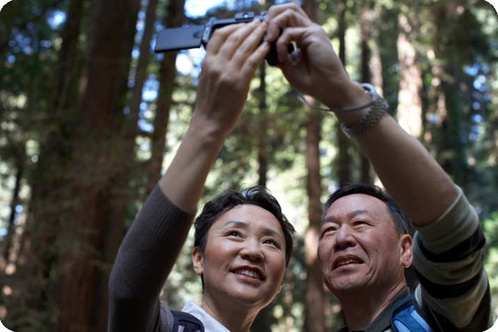 Older couple taking selfie in forest
