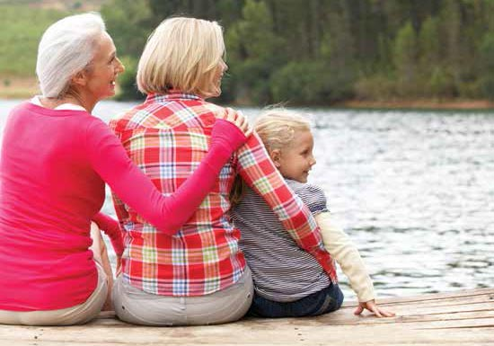 Grandmother, mother and daughter sitting on a dock