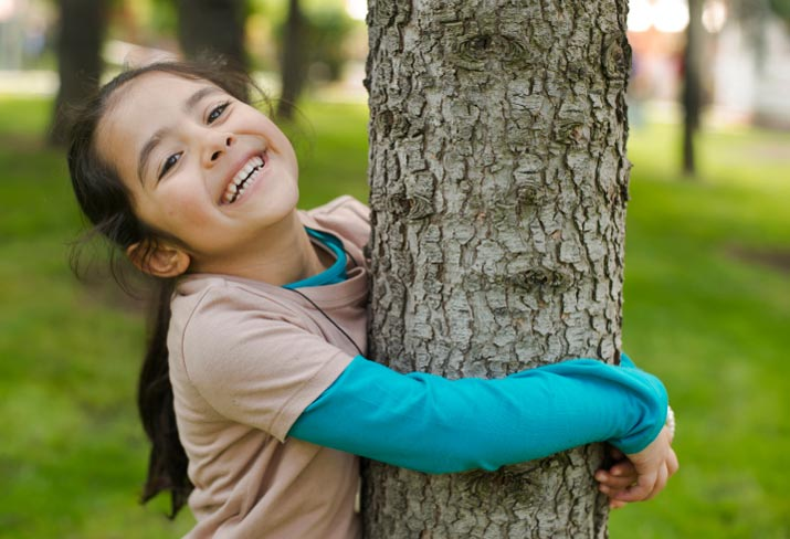 Girl holding tree and smiling